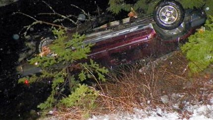 In this photo provided by Maine State Police, an SUV rests upside down in water alongside Route 6 in Kossuth Township, Maine, after Stephen McGouldrick lost control of it on the icy road. Police said Leo Moody, of Kingman, Maine, crawled into the SUV and used a knife to cut the straps off a submerged car seat to pull an infant to safety. The infant was taken to Eastern Maine Medical Center for observation. The two other passengers suffered minor injuries and were treated and released from a hospital.