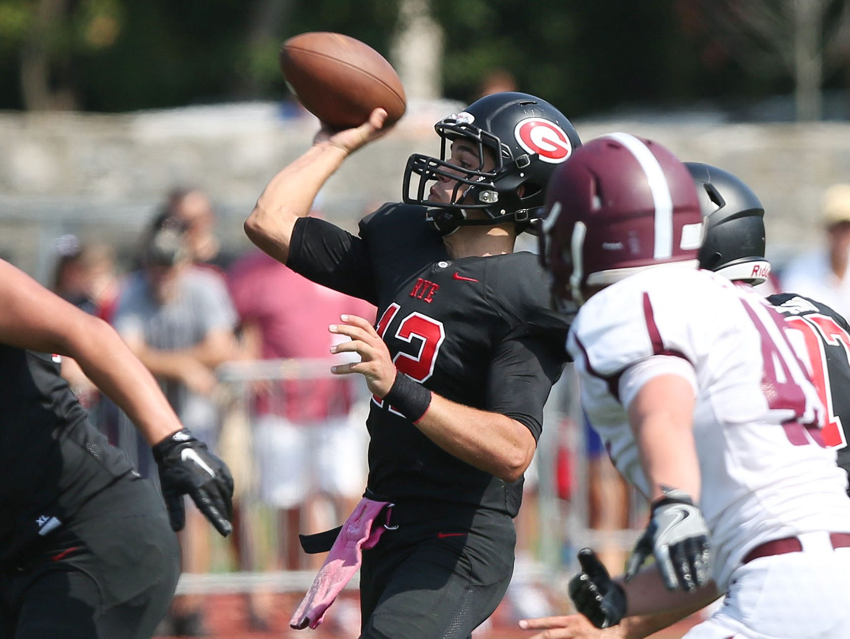 Rye QB T.J. Lavelle throws a pass to Matt Bruno for the Garnets' first touchdown of the game against Harrison during the annual rivalry game at Nugent Stadium at Rye High School on Saturday. Rye won the game 42-12.