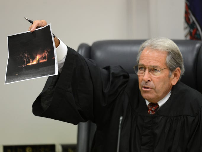 Circuit Judge Glen A. Tyler shows jury members a photograph of the Keller structure fire Tonya S. Bundick is accused of setting with her then boy friend Charles Smith III, during Bundick's arson trial in Virginia Beach, Va. on Monday, July 14, 2014.