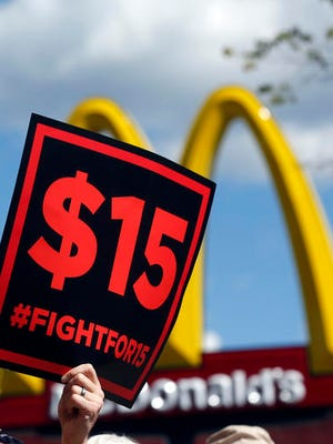 In this 2015 photo, supporters of a $15 minimum wage for fast food workers rally in front of a McDonald's in Albany, N.Y.
