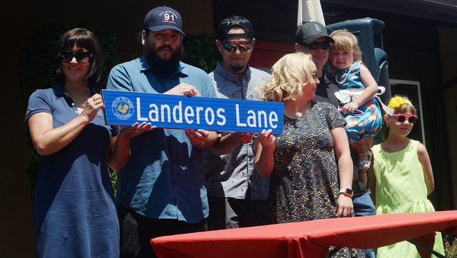 Family members of Rigo Landeros show the sign the city of Fillmore will use to rename a portion of Sespe Avenue in honor of its late fire chief.