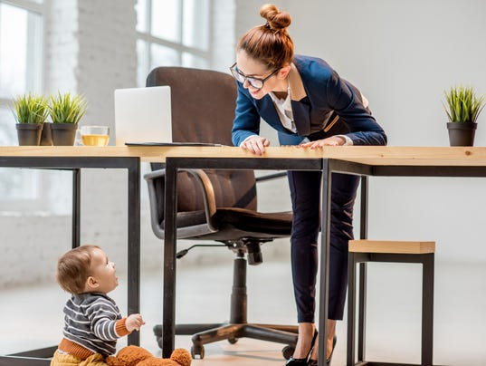 Multitasking businesswoman with her son at the office