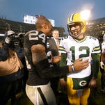 Green Bay Packers quarterback Aaron Rodgers is all smiles as he visits with former teammate and now Oakland Raiders cornerback Charles Woodson (24) after the game at O.co Coliseum stadium.