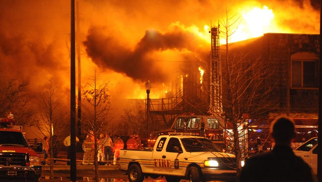Firefighters from multiple departments attack the western edge of a wind-whipped blaze that destroyed four office buildings in downtown Milton and damaged the historic Imogene Theatre on Jan. 6, 2009.