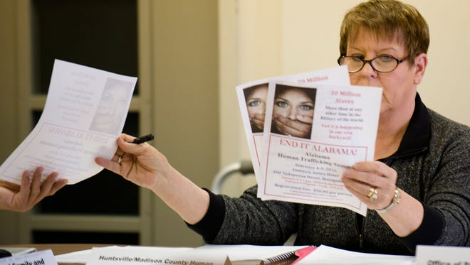 Pat McCay, Huntsville Madison County Human Trafficking representative, passes out flyers during the Alabama Human Trafficking Task Force quarterly meeting at the Alabama State House on Friday, Nov. 6, 2015, in Montgomery, Ala.