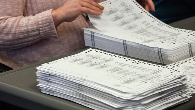 Stacks of ballots are recounted Dec. 5, 2016, at the Benton County Government Center.