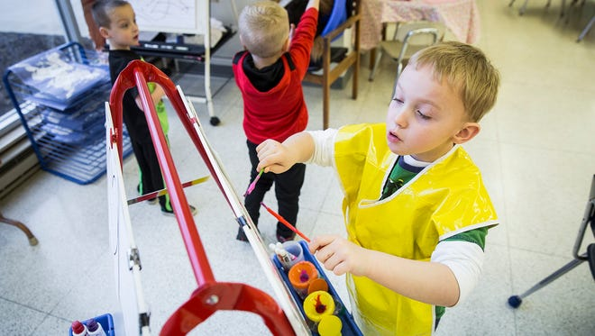 Carter Carmin takes a turn at the painting station at Wes-Del Community School's preschool in a former Star bank in Gaston Wednesday morning.