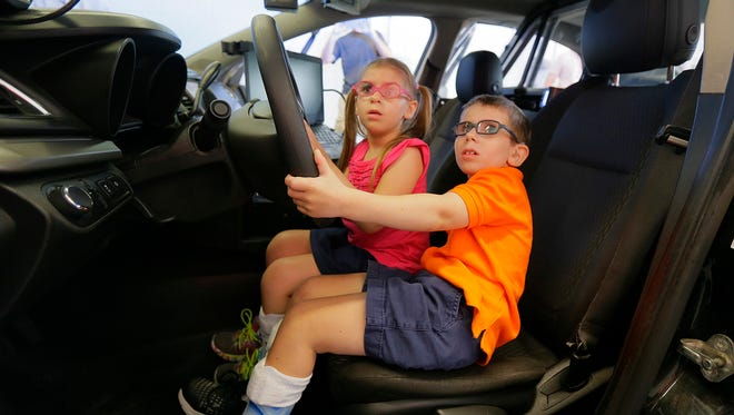 Lara Marini, 6, and Lucas Marini, 9, two siblings of Long Valley who live with Cockayne Syndrome, react to the police car lights during a tour the Washington Township Police Department with their family in Long Valley, NJ Wednesday August 16, 2017.