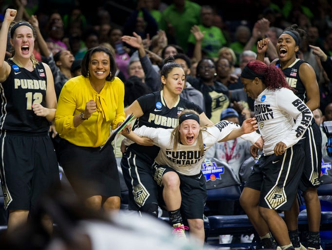 Purdue players celebrate on the bench after a basket
