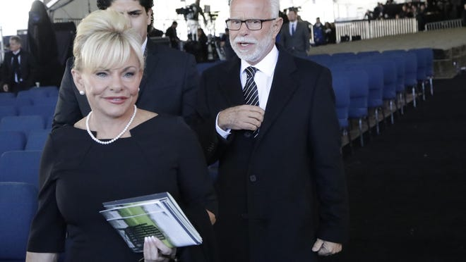 Televangelist Jim Bakker, right, walks with his wife Lori Beth Graham after a 2018 funeral service at the Billy Graham Library for the Rev. Billy Graham. Arkansas is suing Bakker, who is based in Branson, over claims that his products could cure COVID-19.