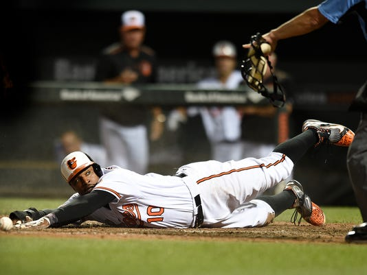 Baltimore Orioles' Adam Jones reaches for the plate after the ball misses the Colorado Rockies catcher Nick Hundley in the 10th inning of a baseball game, Monday, July 25, 2016 in Baltimore. Jones was safe and the Orioles won 3-2. (AP Photo/Gail Burton)