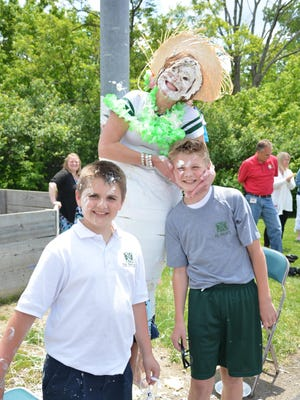 Jackson Gronotte, left, and his brother Trey, right, are shown with St. Pius X Principal Jill Lonnemann after she was duct-taped and received a pie in the face. The Gronottes were top fundraisers in a drive to raise $30,000 for new science curriculum.