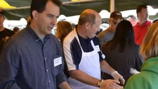 Wisconsin Gov. Scott Walker serves scrambled eggs with ham and cheese as he talks with a customer at the Brown County Breakfast on the Farm at Zirbel Dairy Farms in Glenmore on June 3, 2012.