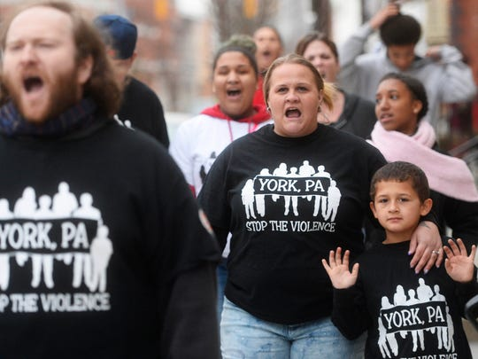 Organizer John Beck, left, is joined by fellow concerned citizens like Ginnie Rivera, center, and her 6-year-old son Richard Dykes as they marched to end violence.