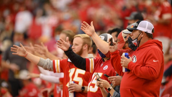 """FILE - In this Oct. 5, 2020, file photo, Kansas City Chiefs fans do """"the chop"""" at the start of the team's NFL football game against the New England Patriots in Kansas City, Mo. The Chiefs barred headdresses and war paint amid the nationwide push for racial justice, but its effort to make its popular """"war chant†more palatable is getting a fresh round of scrutiny from Native American groups as the team prepares to make its second straight Super Bowl appearance."""