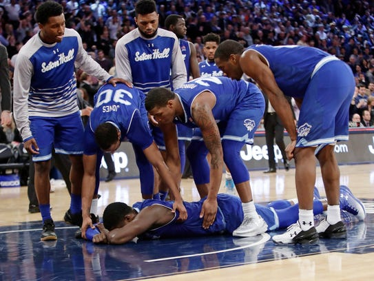 Seton Hall's Angel Delgado, bottom, is consoled by