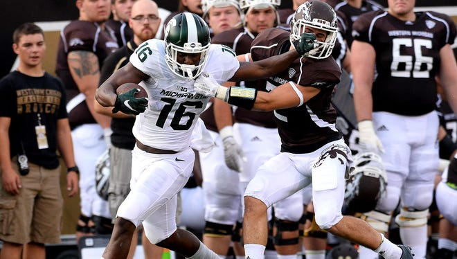 Spartans receiver Aaron Burbridge stiff arms the defender as he works for extra yards in the first quarter Friday against Western Michigan at Waldo Stadium in Kalamazoo.