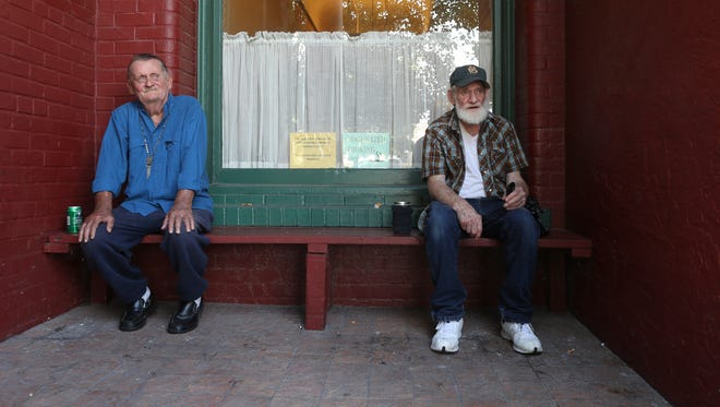 Lorenz Hotel residents Don Tazwell, 73, and John McGowan, 70, sit on a shaded bench outside their building, whose air conditiong is malfunctioning.