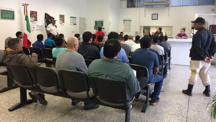 A Mexican immigration employee welcomes a group of