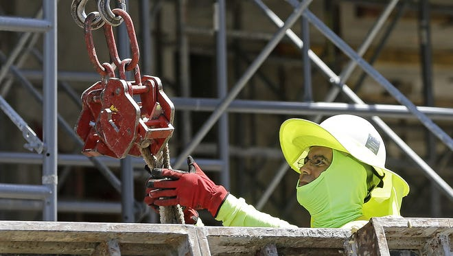 A construction worker continues work on a condominium project in Coral Gables, Fla. On Friday, July 7, 2017, the Labor Department will release the U.S. jobs report for June.