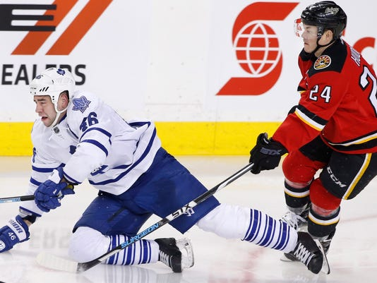 Toronto Maple Leafs' Roman Polak, left, from Czech Republic, is knocked down by Calgary Flames' Jiri Hudler, from Czech Republic, during second period NHL action in Calgary, Alberta, Tuesday, Feb. 9, 2016. (Larry MacDougal/The Canadian Press via AP) MANDATORY CREDIT