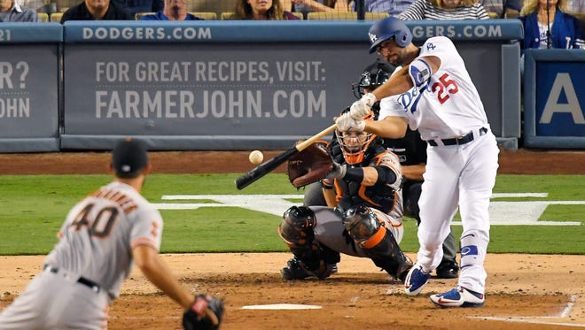 Los Angeles Dodgers' Rob Segedin, right, hits a solo home run off San Francisco Giants starting pitcher Madison Bumgarner, left, as catcher Buster Posey watches during the second inning of a baseball game, Tuesday, Aug. 23, 2016, in Los Angeles.