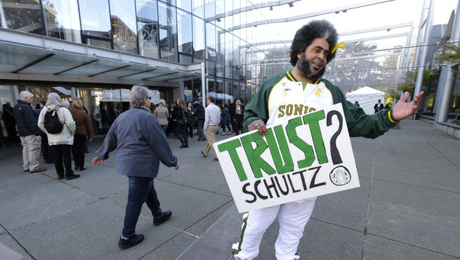 """In this March 18, 2015 file photo, Kris Brannon, who is known as """"Sonics Guy"""" for his efforts to bring an NBA basketball team back to Seattle, holds a sign that reads """"Trust Schultz?"""" as he greets attendees arriving for Starbucks Corp.'s annual shareholders meeting in Seattle."""
