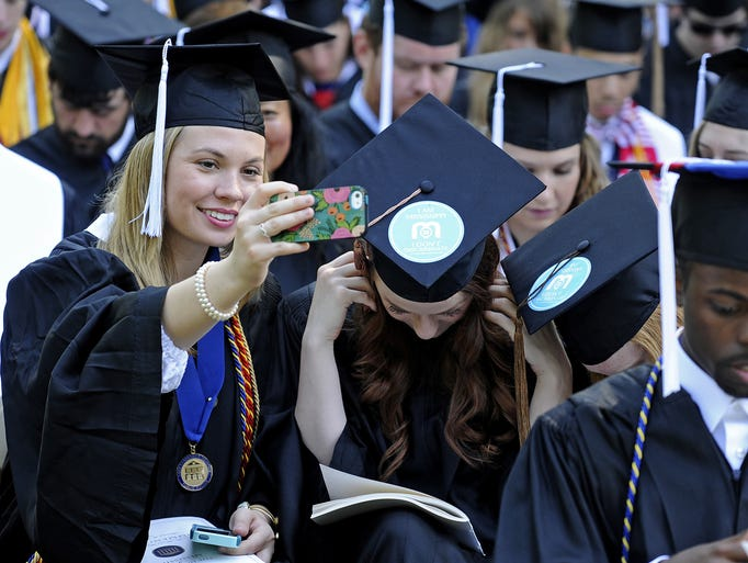 Graduates take photos showing stickers protesting the speaker, Mississippi Gov. Phil Bryant, during a commencement ceremony in Oxford, Miss., Saturday, May 10, 2014.