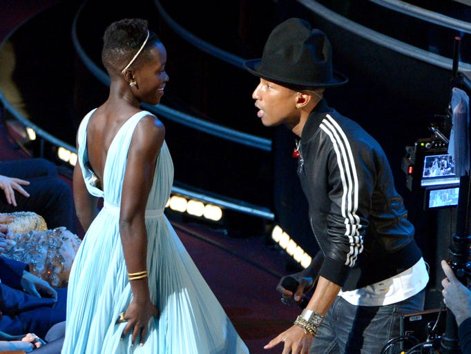 "Lupita Nyong'o, left, dances with Pharrell Williams during his performance of ""Happy"" at the Oscars at the Dolby Theatre on March 2 in Los Angeles."