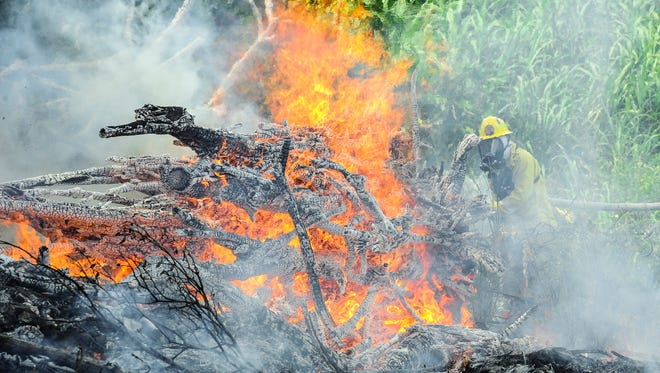 In this file photo, Guam Fire Department firefighter Christopher Florig prepares to douse a fire with water as he and other firemen battle a blaze near the Hagåtña pool.