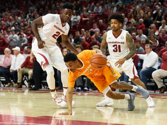 Arkansas defenders Adrio Bailey, left, and Anton Beard, right, put the pressure on Tennessee guard James Daniel III, center, as he tries to take the ball up the court during the first half of an NCAA college basketball game Saturday, Dec. 30, 2017 in Fayetteville, Ark. (AP Photo/Michael Woods)