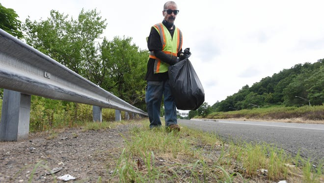 Paterson resident Benino Gonzalez picks up trash on Rt 19 in Paterson.