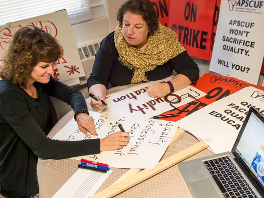 Cheryl Slattery, left, and Lynn Baynum, both associate professors of teacher education at Shippensburg University, work on signs on Thursday, Sept. 29, 2016. The signs will be used if the professors go on strike if negotiations between the State System of Higher Education and the Association of Pennsylvania State College and University Faculty continue unsuccessfully.
