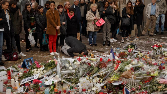 A Muslim, center, prays in front of a floral tributes near the Bataclan concert hall Monday after the terrorist attacks in Paris.  France is urging its European partners to move swiftly to boost intelligence sharing, fight arms trafficking and terror financing in the wake of the Paris attacks.