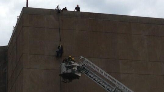 Crews from the Des Moines Fire Department work to rescue a maintenance worker dangling from the Hoover State Office Building in Des Moines on Friday, June 27, 2014.