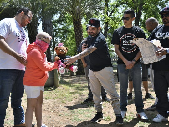 Members of NVUS car club gives Amanda Aceves a teddy