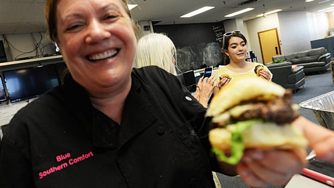 Carolyn Manning, chef and owner of Blue Southern Comfort Foods, poses with one of her 'better burgers' in The Times' newsroom.