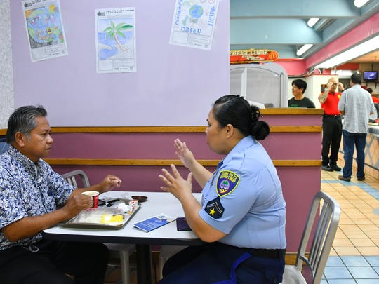 Officer Susie Santos talks with Mario Fortes, 61, of Tamuning, during the Guam Police Department's outreach, Coffee with a Cop, at the Tamuning McDonald's on Jan. 25, 2017. Fortes said he expressed his frustration at the lack of progress on an accident report from more than a year ago. Fortes said his car was damaged in a hit-and-run, and he reported the license plate number of the suspected vehicle, but action was yet to be taken by law enforcement.