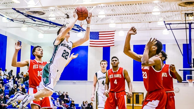 Riley Lewis ,22, of Williamston takes the ball to the basket for 2 points past Cedric Dunbar ,right, of Troy Athens during their Holiday Hoops Invitational game Tuesday December 29, 2015 at Lansing Community College. KEVIN W. FOWLER PHOTO