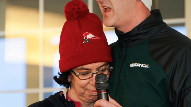 A tear falls from Kristine Kuhnert's eye as family-friend Luke Wilcox speaks about his friend and her late-husband Dr. Scott Kuhnert prior to the start of the second-annual Playmakers Holiday Classic 5K on Wednesday. Scott Kuhnert, an anesthesiologist and Bath Township resident, was killed in a head-on collision with a drunk driver on Dec. 5.