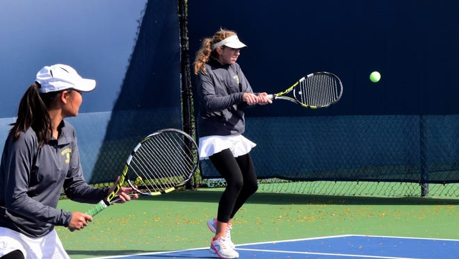 Jillian Blatt of Seven Hills (back) keeps the game going with a two-handed bankhand return, October 21.
