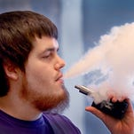 Josh Maynard, an employee at Indy Vapor Shop, takes a break to smoke his e-cigarette.