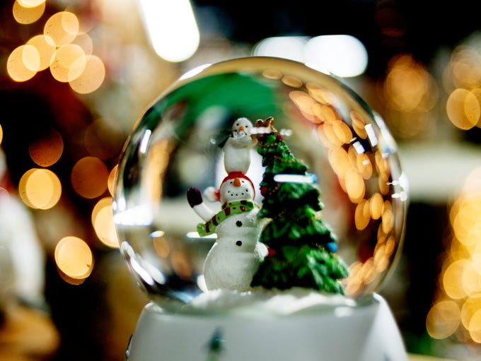 A snow globe with a snow person is seen for sale at