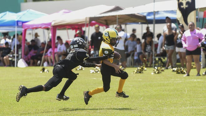 Cinnabon Saints Xavier Walker (10) attempts to tackle Josiah Binondo (0) of the Dr. Shieh Packers during their Triple J Ford Guam Nationl Youth Football Federation league game at the University of Guam field in Mangilao on Sept. 5. Frank San Nicolas/Pacific Daily News/fsannicola@guampdn.com