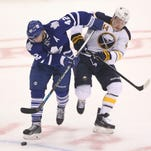 Toronto Maple Leafs center Tyler Bozak (42) battles for the puck with Buffalo Sabres left wing Nicolas Deslauriers (44) at Air Canada Centre.