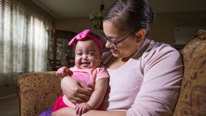 Mia Welch holds her baby daughter, Malaya Soares, 10 months, at home on March 7, 2018. Malaya received her heart transplant on Dec. 14, 2017.