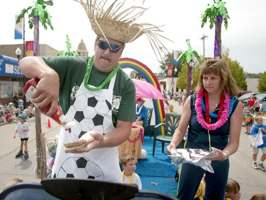 Greg and Donna Sprangers grill, garnish and wrap hamburgers, for throwing to the gathered crowed, while riding on the Thunder Area Soccer float in the Seymour Hamburger Festival parade.
