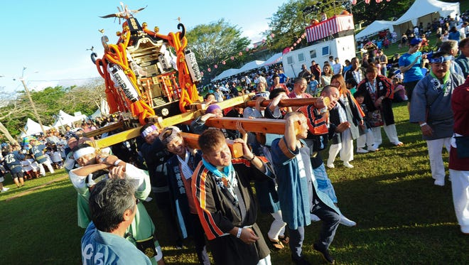 Men carry a mikoshi, or portable shrine, through the crowd at the 34th Annual Autumn Festival in the Ypao Beach Park at Tumon on Nov. 30, 2014. The festival, hosted by the Japan Club of Guam, has been postponed due to Tropical Storm In-Fa.