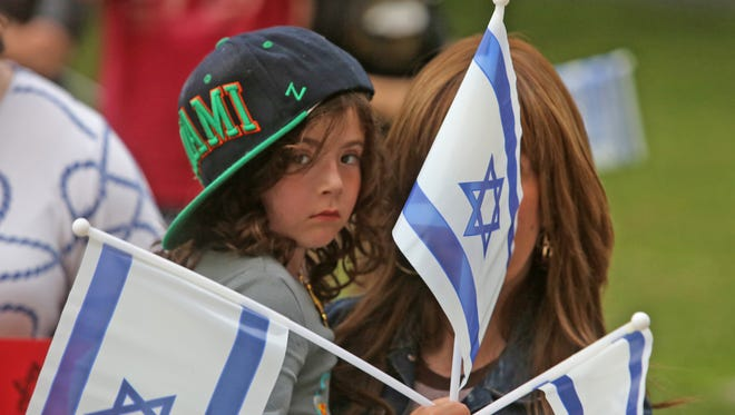 Esther Weinstein, 5, of New Hempstead, is held by her mother, Leah, as they were among the hundreds of people who attended a rally in support of Israel at the Rockland County Courthouse in New City July 10, 2014. The rally was organized by the Jewish Federation of Rockland County.