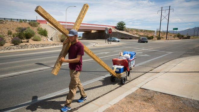 Mitchell Manning carries a 12-foot cross made of Western red-cedar near U.S. Route 70 in Las Cruces, NM, as he heads from Florida to California, Tuesday, August 9, 2016.
